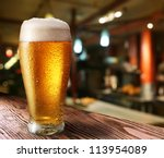 Stock photo glass of light beer on a dark pub 113954089