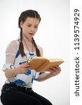 young pretty schoolgirl sitting ... | Shutterstock . vector #1139574929