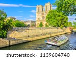 Small photo of Paris, France - July 1, 2017: Bateaux-Mouches with many tourist during a trip at sunset on River Seine with Cathedral of Notre Dame on the Ile de la Cite on background. Sunny day, blue sky.