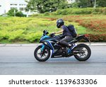 Small photo of A biker riding a Kawasaki Eva motorcycle on Hiram's Highway in Sai Kung ,Hong Kong and with blur background ,Photo taken on 22 July 2018