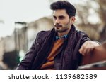 thoughtful young man sitting on ... | Shutterstock . vector #1139682389