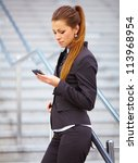 Businesswoman in suit with suitcase using mobile phone - stock photo