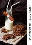 Chocolate cookies with oat flakes and spiced milk. - stock photo