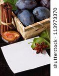 Fresh plums and spices with paper for notes. - stock photo