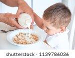 little boy helps dad pour milk... | Shutterstock . vector #1139786036