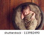 Newborn Baby In A Round Wood...