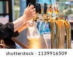 barman hands pouring a lager... | Shutterstock . vector #1139916509