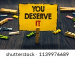 Small photo of Word writing text You Deserve It. Business concept for Reward for something well done Deserve Recognition award Blacky wooden desk laid paper clip randomly one hold yellow board with text.