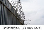 barbed wire along the fence    ... | Shutterstock . vector #1140074276
