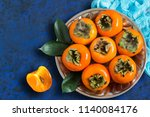 ripe persimmon on metal plate... | Shutterstock . vector #1140084176