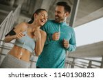 young couple running in the... | Shutterstock . vector #1140130823
