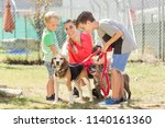 mom with her sons walking dogs... | Shutterstock . vector #1140161360