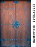 Old Wooden Door With Round Iro...