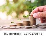 hand putting coin on dollar... | Shutterstock . vector #1140170546