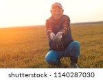 senior farmer in wheat field... | Shutterstock . vector #1140287030