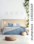 pouf in front of blue bed with... | Shutterstock . vector #1140318269