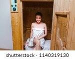 woman sitting in sauna room in... | Shutterstock . vector #1140319130