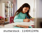 young girl sitting at desk in... | Shutterstock . vector #1140412496