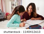 mother helping daughter with... | Shutterstock . vector #1140412613