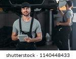 happy mechanic in overalls...   Shutterstock . vector #1140448433