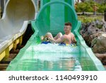 young man ride on a slide in a... | Shutterstock . vector #1140493910