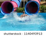 young man ride on a slide in a... | Shutterstock . vector #1140493913