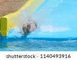 young man ride on a slide in a... | Shutterstock . vector #1140493916