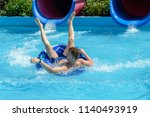 young man ride on a slide in a... | Shutterstock . vector #1140493919