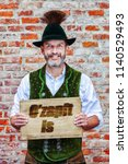 handsome bavarian man holding a ... | Shutterstock . vector #1140529493
