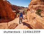 hiker rests in arches national... | Shutterstock . vector #1140613559