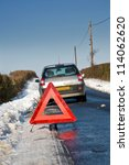 Broken down motor vehicle with red warning triangle in winter snow conditions - stock photo