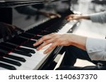 Male pianist hands on grand...
