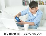 boy playing computer game with... | Shutterstock . vector #1140703079