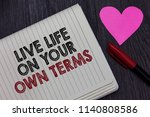 Small photo of Writing note showing Live Life On Your Own Terms. Business photo showcasing Give yourself guidelines for a good living Strikethrough words on notepad love heart pen on blackish woody desk.