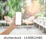 hand s holding phone blurred... | Shutterstock . vector #1140812480