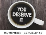 Small photo of Word writing text You Deserve It. Business concept for Reward for something well done Deserve Recognition award Black coffee with coffee mug floating texts on gray black wooden desk.