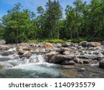 a clear stream flowing through... | Shutterstock . vector #1140935579