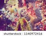 young girl shopping at festive... | Shutterstock . vector #1140972416