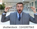 excited businessman holding two ...   Shutterstock . vector #1141007063