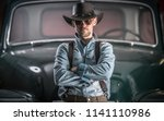 Men and the Classic Car. Caucasian Cowboy Looking Guy in Front of His Classic Ride. - stock photo