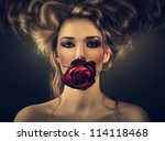 woman with red rose and drops in hair in dark - stock photo