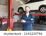 smiling repairman in uniform... | Shutterstock . vector #1141225796