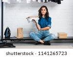 smiling female designer sitting ... | Shutterstock . vector #1141265723