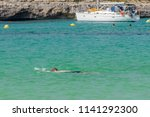 man in a scuba mask swims in... | Shutterstock . vector #1141292300