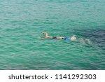 man in a scuba mask swims in... | Shutterstock . vector #1141292303