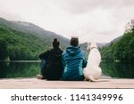 couple with dog sitting on dock ... | Shutterstock . vector #1141349996