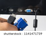 Man S Hand Holds Hdmi And Vga...