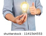 hand holding a light bulb with... | Shutterstock . vector #1141564553