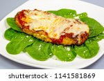 chicken parmesan on a bed of... | Shutterstock . vector #1141581869