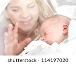 Newborn baby boy sleeping in a bed. His mother looking at. Close up with shallow DOF. - stock photo